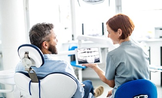 Dentist and patient smiling as they discuss X-ray on tablet