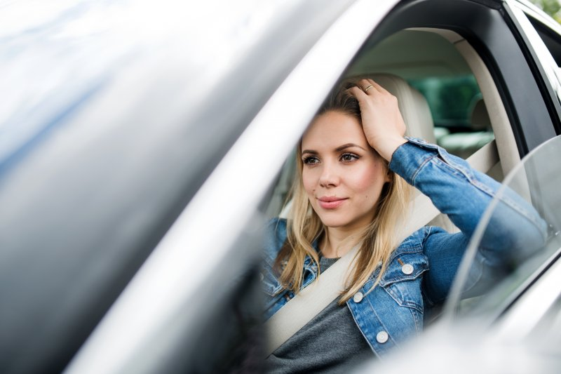 a woman sitting in her vehicle while waiting for her dentist's appointment