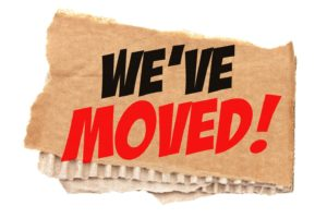 """We've Moved"" in bold lettering on piece of cardboard"