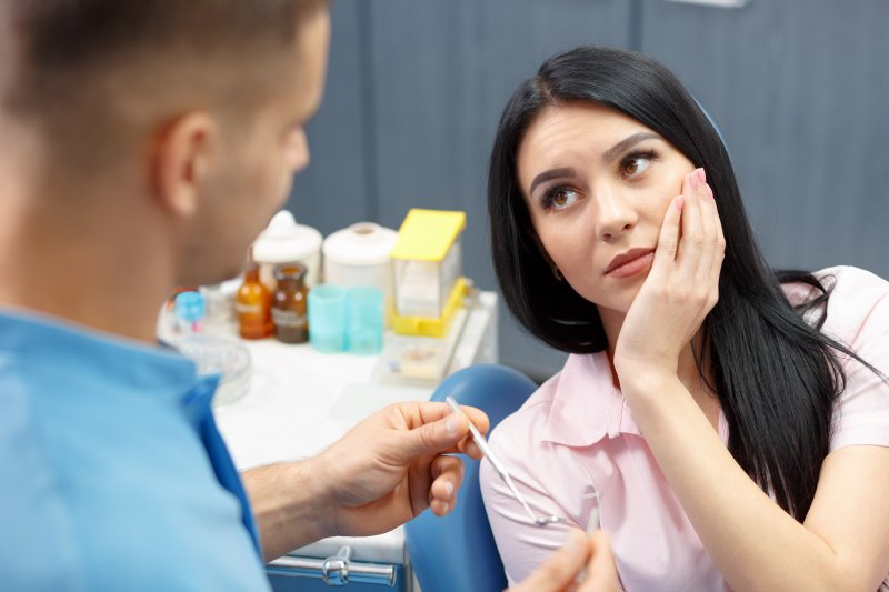 a young woman holding her cheek in pain while listening to a dentist explain the need for a root canal