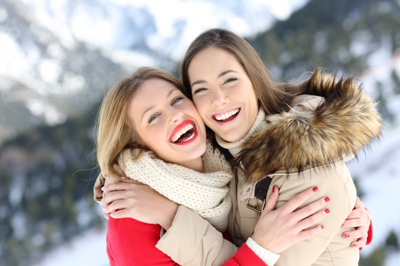 two young females standing outside in the snow wearing coats and smiling after receiving teeth whitening treatments