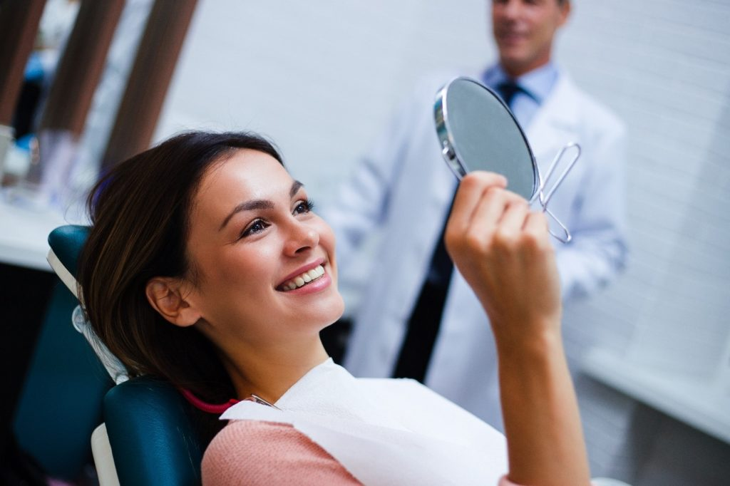 Patient with dental crowns looking at smile in dentist's mirror